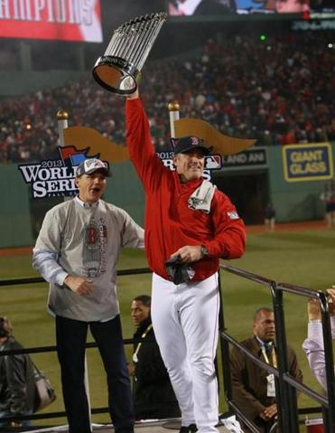 Red Sox manager John Farrell held up the World Series trophy, general manager Ben Cherington by his side.