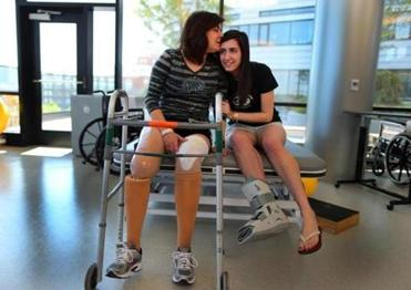 Celeste Corcoran kissed her daughter, Sydney, at Spaulding Rehabilitation Hospital in June. She lost both legs in the Marathon bombing.