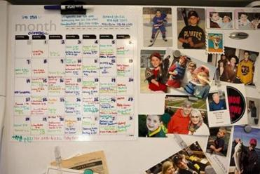 The family calendar, color-coded for sports, on the Heneys' refrigerator. Four of the five children take part in four different sports.