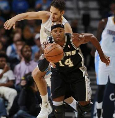 San Antonio Spurs forward Corey Maggette, front, pulls in a loose ball in front of Denver Nuggets guard Evan Fournier in the fourth quarter of the Nuggets' 98-94 victory in an NBA preseason basketball game in Denver on Monday, Oct. 14, 2013. (AP Photo/David Zalubowski)
