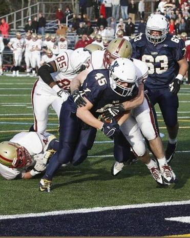 Xaverian's Kenny Kern carries the ball — and a BC High defender — into the end zone for the key 2-point conversion in overtime.