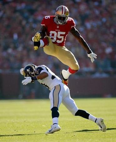 49ers tight end Vernon Davis, who had 82 yards receiving and a TD, goes high to evade Rams safety Rodney McLeod.