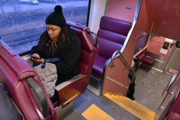 Jeannette Akers of Dorchester checks her phone while riding the train to Lynn.