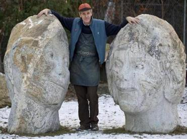 "Sculptor Joe Wheelwright standing next to his granite pieces called ""Loving Stones,"" outside the deCordova Sculpture Garden and Museum."