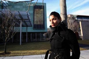 "Artist Hamra Abbas in front of ""Wall Hanging I"" on the facade of the Isabella Stewart Gardner Museum."