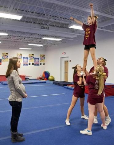 Team members practice a pyramid at All That Cheer and Tumble, while Jessica Reed, a coach,  looks on.