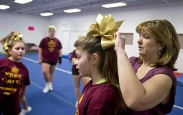 Newburyport Youth Cheerleaders coach Hollis Caswell tied a bow on Lily Sakaniwa's hair before their practice.
