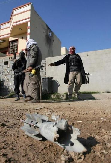 Gunmen patrolled near an exploded mortar shell during clashes in Fallujah on Thursday.