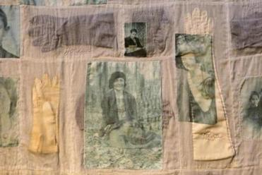 "Detail of quilt ""The Raitzyns,"" with each glove's color reflecting whether the photo's subject survived the Holocaust."