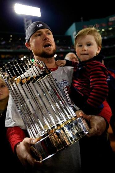 Jon Lester holds two valuable properties — the World Series trophy and his son Hudson — after the Red Sox clinched the title last fall.. (Photo by Jamie Squire/Getty Images)