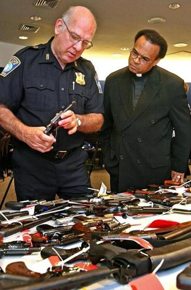 Boston Police Superintendent-in-Chief Albert Goslin,left, and  Reverend Shawn Harrison examined one of 382 firearms turned in during a gun buyback in Boston in 2006.