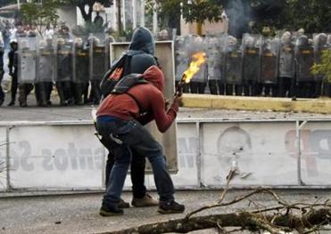 Activists prepared to throw a firebombs at National Guard troopers in riot gear during a protest in San Cristobal.