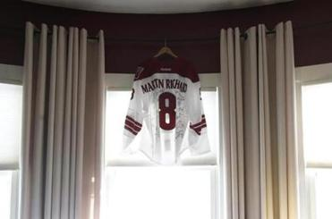 A jersey worn by Boston native and Phoenix Coyotes player Keith Yandle hangs in the living room of the Richard's family home in Dorchester, Massachusetts February 25, 2014. (Jessica Rinaldi/Globe Staff)
