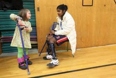 Nina plays with her big sister Joita's crutches after watching her play basketball at an away game.
