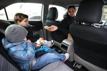 Angela Errico gave her son, Ian (left), a treat from Sullivan's on Thursday as Kyle Vieira munched on a hot dog.