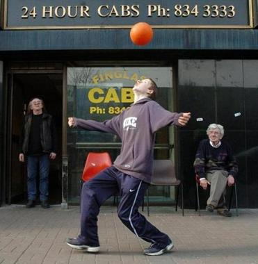 Elderly men watch a youngster play with a ball in Dublin in 2004.