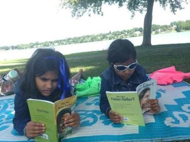 Jia Kumar, 8, and her sister Bela, 6, read historical biographies at Lake Quannapowitt in Wakefield last summer.