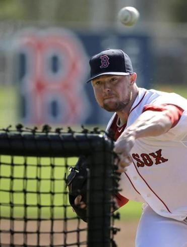 Boston Red Sox starting pitcher Jon Lester delivers a throw during spring training baseball practice, Sunday, Feb. 23, 2014, in Fort Myers, Fla. (AP Photo/Steven Senne)