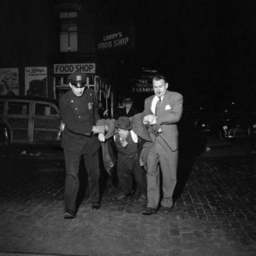 This photo of a man being dragged by police at night shows Maier's talent for unposed street photography.