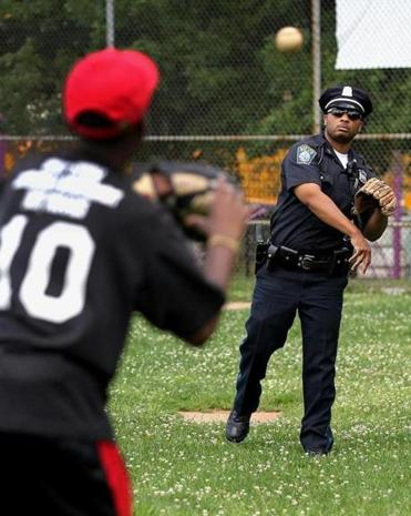 Officer Dennis O. Simmonds (right) tossed a ball with Teshawn Coleman in 2011. Simmonds died after a medical emergency, police said.