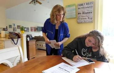 Elayne Daniels at home in Canton checking on her daughter Rebecca, 15, as she starts her homework.