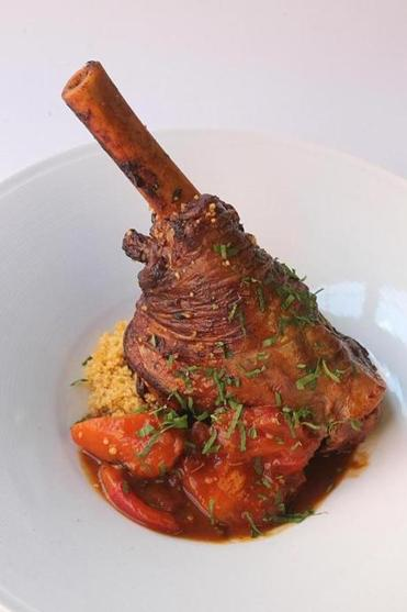 Moroccan-style lamb with couscous, roast tomato, preserved lemon, and harissa.