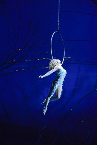 "A performer, using her neck to balance, hangs from a hoop  in ""Amaluna."""
