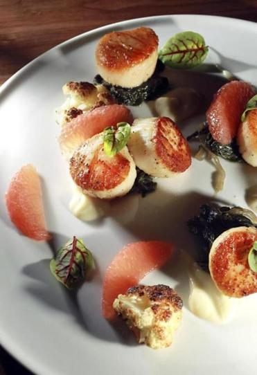 Seared scallops entree with cauliflower, grapefruit, Swiss chard, and bacon.