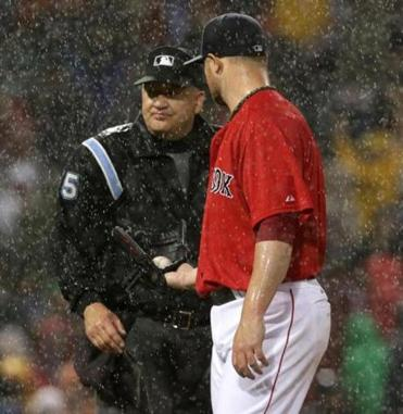 Jon Lester handed the ball to home plate umpire Jeff Nelson as rain delayed the game.