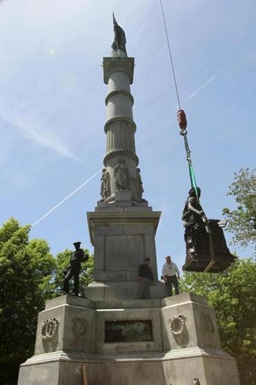 Workers hoisted one of four statues that were restored to Boston Common Thursday afternoon.