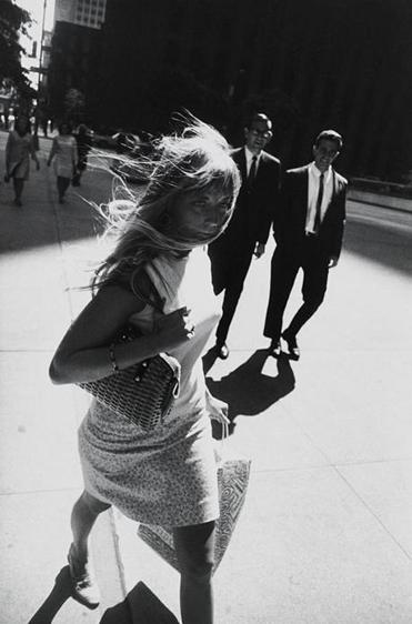 Garry Winogrand photographed this woman (and the grinning men behind her) on a New York sidewalk in 1965.