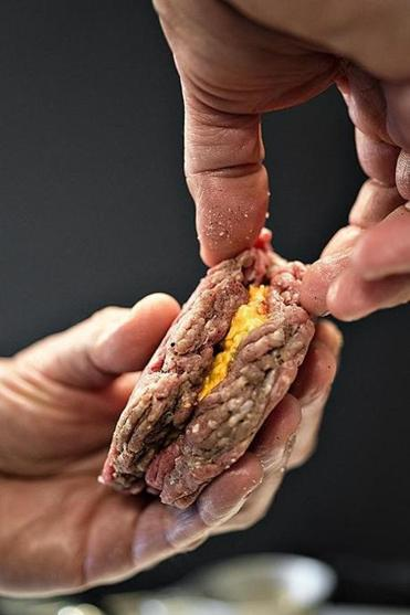 TIP: Work carefully when you pinch the two patties closed over the filling, making sure to seal them and prevent the cheese from leaking out while the burger cooks.