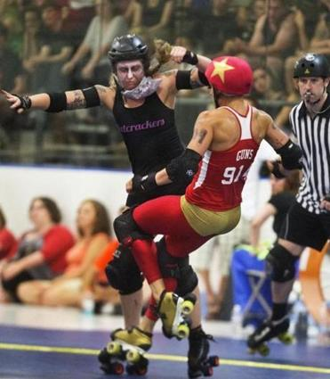 Aubrey Planitz of the Nutcrackers (left) sends Candy Saunders of the Wicked Pissahs to the deck during the roller derby season opener at Simoni Ice Rink in Cambridge, July 13, 2014.