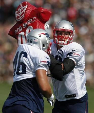 New England Patriots tight end Rob Gronkowski, right, runs a drill with running back James Develin during NFL football training camp in Foxborough, Mass., Saturday, July 26, 2014. (AP Photo)
