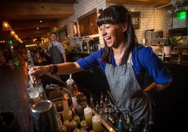 Bartender Tainah Soares is among the Alden & Harlow staff outfitted in aprons of various brands by owner Michael Scelfo.
