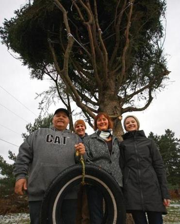 The MacPhersons (from left), John, Tyler, Ethel Ann, and Jessica, with their tree and the old tire swing.