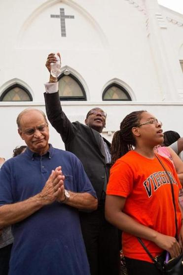 Charleston residents gathered and sung together outside the historic Emanuel African Methodist Episcopal Church on Friday to honor the nine victims slain by alleged killer Dylann Roof.