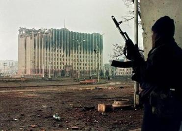 A Chechen fighter took cover from sniper fire in Grozny in 1995. Across the square, the presidential palace sat in ruins after Russian artillery bombardments.