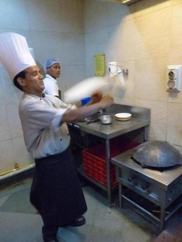 A Kebabs and Kurries chef tosses a roti in the air.