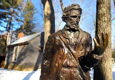 A statue of Henry David Thoreau in front of a reproduction of his cabin at the Walden Pond Reservation.