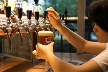 One of the waitresses in Master Gao's backyard expertly poured a beer for a customer. Gao's staff has been trained to understand beer and its subtleties.
