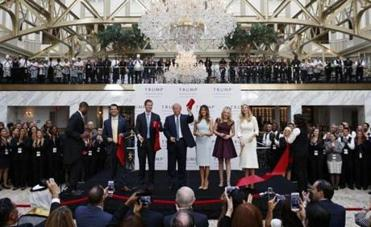 As his campaign flags, Trump cuts a hotel ribbon