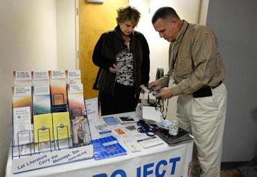 "Plymouth 11/30/2016 : As part of Project Outreach, the New testament Church of Cedarville hosted a ""drop-in center'. The program brings together police departments, health care providers, and nonprofits in an effort to help tackle the opiod crisis. Volunteer Lisa Robinson and Plymouth Police Chief Mike Botieri (cq) set up the Project Outreach table. Photo by Debee Tlumacki for the Boston Globe (south)"
