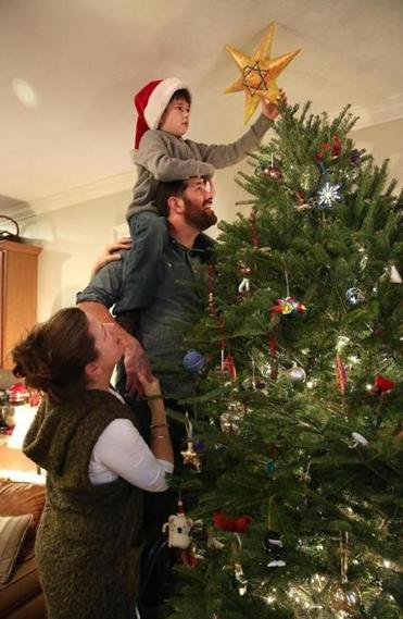 Karolyn Feeks Maws, a Christian, and her Jewish husband Tony Maws decorated their Christmas tree, with their 8-year-old son Charlie Maws, who is being raised in both traditions.