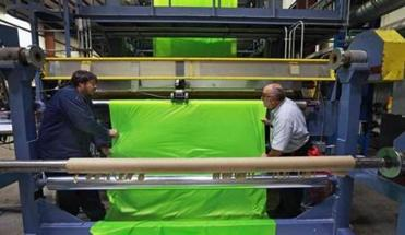 Workers Mike Champoux and Joe Castelo (above) operated a machine producing recreational parachute material at chemical manufacturing company Bradford Industries in Lowell.
