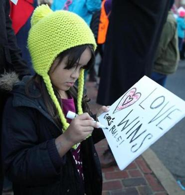 Isla Nava , 5, of Cambridge works on her sign at the Women's March on Boston.