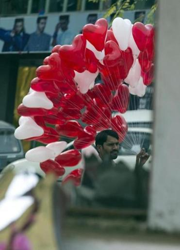 A Pakistani vendor, seen in a mirror, sells heart-shaped balloons at a flower market, to celebrate Valentine's Day, in Islamabad, Pakistan, Tuesday, Feb. 14, 2017. A Pakistani judge has banned Valentine's Day celebrations in the country's capital, saying they are against Islamic teachings. A court official says the judge ruled on a petition seeking to ban public celebrations. Islamist and rightwing parties in Pakistan view Valentine's Day as a vulgar Western import. (AP Photo/B.K. Bangash)