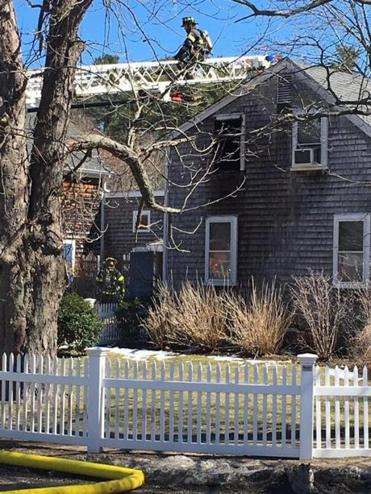 Firefighters work to extinguish a second-floor fire on Temple Street in Duxbury.