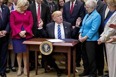 Trump was made to sign bills on a very small desk today