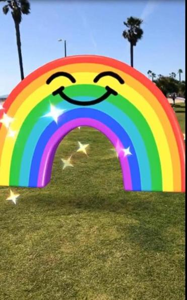 A smiley rainbow from Snapchat's World Lenses app brightens up an outside photo.